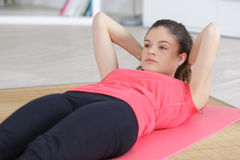 Beautiful doing sit ups on mattress at home Stock Images