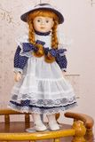 Beautiful doll. Doll in a blue dress with an apron royalty free stock photo