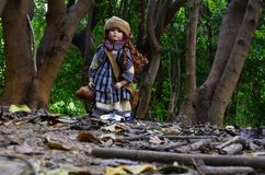 Beautiful doll in the forest royalty free stock photography