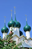 Beautiful domes of orthodox church with an apple-tree branch before them. Royalty Free Stock Photos