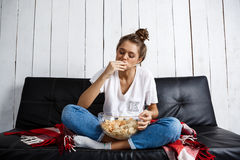 Beautiful domestic girl eating chips, watching tv, sitting at sofa. Stock Photo