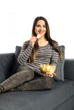 Beautiful domestic girl eating chips, watching tv, sitting at sofa on white Royalty Free Stock Image