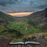 Beautiful dramatic landscape image of Nant Francon valley in Snowdonia during sunset in Autumn coming out of pages of open story. Beautiful moody landscape image royalty free stock images