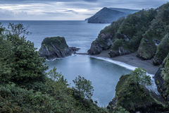 Beautiful dramatic sunrise landsape image of small secluded cove Royalty Free Stock Photo
