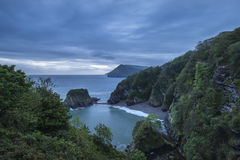 Beautiful dramatic sunrise landsape image of small secluded cove Royalty Free Stock Photos