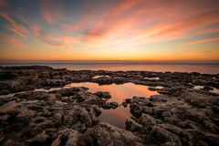 Beautiful dramatic sunrise on the rocky beach Royalty Free Stock Images