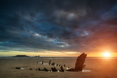 Beautiful dramatic sunset landscape over shipwreck on Rhosilli  Royalty Free Stock Image
