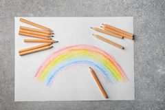 Beautiful drawing of rainbow and color pencils. On grey background Royalty Free Stock Images