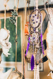 Beautiful dream catcher with purple hackle. Hanging with other decoration elements. Showcase of modern art installation in museum Royalty Free Stock Images