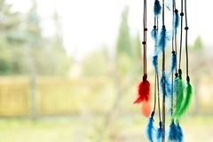 Beautiful dream catcher by a window with blue, green and red fea. Thers Royalty Free Stock Image