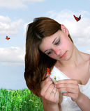 Beautiful Dreamer. Teenage girl sitting in a meadow pulling petals from a daisy....loves me love me not Royalty Free Stock Photography