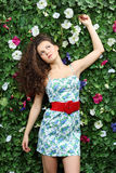 Beautiful dreaming woman with curly hair stands next to hedge Stock Photos