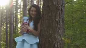 Beautiful dreaming woman lean on tree trunk in forest holding her shoes in hands. Beautiful woman in blue dress lean on tree in the forest holding red shoes on stock footage