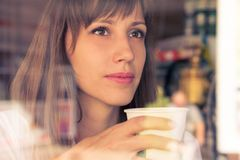 Beautiful dreaming young girl with cup of coffee. Warm color toned image Royalty Free Stock Photo