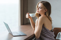Beautiful dreaming young woman with laptop drinking coffe Royalty Free Stock Image