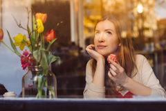 Beautiful dreaming young woman sitting in coffee shop near the window and eating dessert Stock Photos