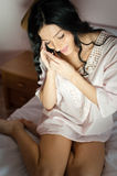 Beautiful dreamy cute brunette girl happy smiling talking on mobile phone in bed portrait image Stock Photography