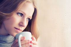 Beautiful dreamy girl with a cup of hot coffee at the window Stock Photos