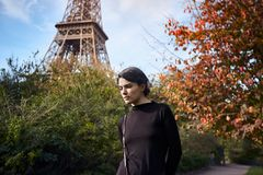 Beautiful dreamy girl posing on the background of the Eiffel Tower. Paris, Champ de Mars. Beautiful stylish, dreamy girl in black dress with backpack posing on stock photo