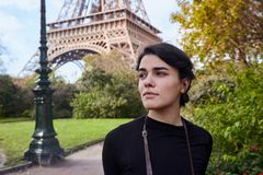Beautiful dreamy girl posing on the background of the Eiffel Tower. Paris, Champ de Mars. Beautiful stylish, dreamy girl in black dress with backpack posing on royalty free stock images
