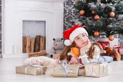 Beautiful girl in santa hat unwrapping christmas presents Royalty Free Stock Images