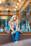 Beautiful dreamy woman relaxing after walking in urban setting during free time, attractive girl with trendy look posing outdoors Royalty Free Stock Photos