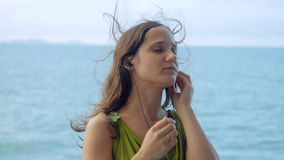 Beautiful dreamy young woman listening to music on headphones on the sailing ship Stock Photo