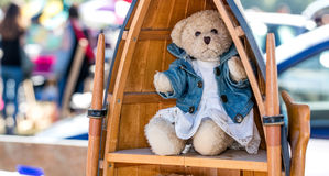 Beautiful dressed up teddy bear for nostalgia second hand use. Beautiful dressed up teddy bear displayed in wooden library in boat shape for nostalgia second Stock Images