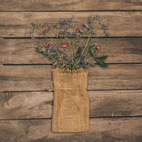 Beautiful dried flowers arranged in sack bag on rustic wooden table Royalty Free Stock Photography