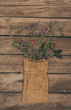 Beautiful dried flowers arranged in sack bag on wooden table top Royalty Free Stock Images