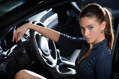 Beautiful driver portrait. Perfect woman driver sitting relaxed in a car, with her hand on steering wheel. Automobile salon background Stock Images