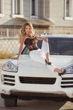 Beautiful driver Sexy girl model sitting on white bonnet of luxu Royalty Free Stock Photos