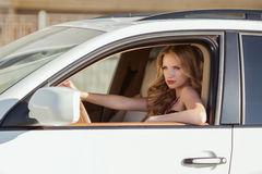 Beautiful driver woman in car indoor keeps wheel looking into th Stock Images