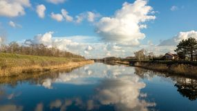 Beautiful drone shot of a river with cloudy sky reflecting in th. Beautiful drone shot of a river with cloudy blue sky reflecting in the water Royalty Free Stock Photos