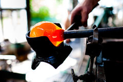 Beautiful drop of liquid glass, first step of glass blowing. Glass blower Stock Images