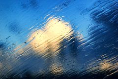 Beautiful drops on a glass against a blue sky with sun and clouds. Clear glass stock photo