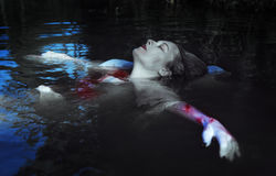 Beautiful drowned woman in bloody dress lying in the water Royalty Free Stock Photography