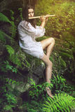 Beautiful dryad playing a flute. In the forest. Romance and fantasy Stock Images