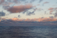 Beautiful dusk clouds at sea. Orange tinged clouds over reflective evening ocean Royalty Free Stock Images