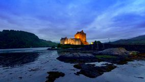 Beautiful dusk at illuminated Eilean Donan Castle over the lake, Scotland stock footage