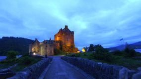 Beautiful dusk at illuminated Eilean Donan Castle over the lake in Scotland stock video footage
