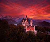 Beautiful early morning view of the Neuschwanstein fairy tale castle, bloody dark sky with autumn colours in the trees during sunr. Ise. Bavaria, Germany Royalty Free Stock Photos
