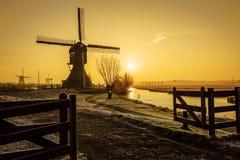 Warm and frozen windmill sunrise. Beautiful early morning and warm Kinderdijk sunrise on windmills and loading platform nearby Alblasserdam and Rotterdam Stock Photos