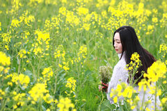 At beautiful early spring, a young woman stand in the middle of yellow rape flowers filed which is the biggest in Shanghai. A young woman stand in the middle of Stock Images