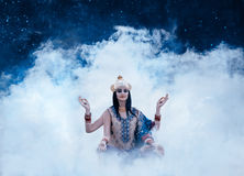Beautiful east exterior girl. Sitting in the smoke depicting eastern deity, indian, shiva, fashion creative color toning Royalty Free Stock Photo