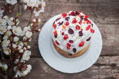 Beautiful Easter cake stands on a wooden surface, in the background the blooming apricot. Easter sweet bread Orthodox kulich, paska, willow twigs. Easter Stock Images