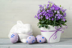 Beautiful easter decoration with Campanula flowers, Easter eggs and ceramic rabbit, on white wooden background Royalty Free Stock Photography