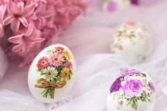 Easter eggs decorated with paper napkins and flowers on white tulle background; decoupage technique royalty free stock images