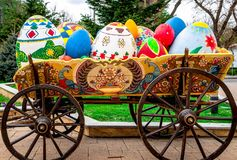 Beautiful easter eggs in old truck with big wheels in the park. Large decorative multicolored beautiful easter eggs in old truck with big wheels in the park stock image