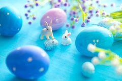 Beautiful Easter eggs with rabbits toy and flowers on blue wooden background, closeup. Easter holiday concept Royalty Free Stock Photography